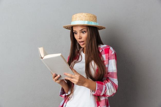 Ciérrese encima del retrato de una mujer joven asombrada en sombrero de paja que lee un libro