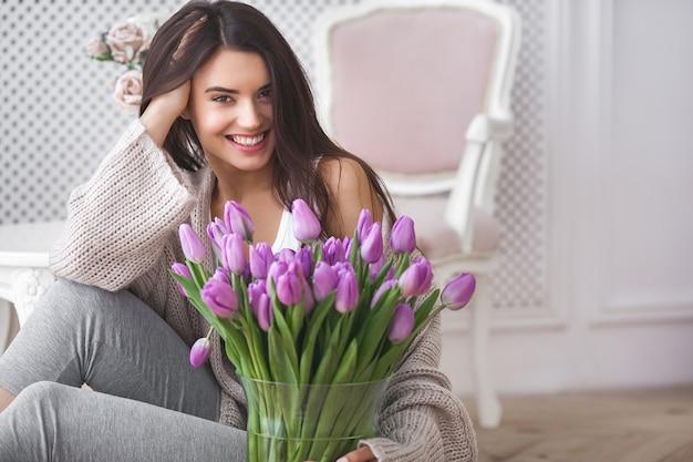 Ciérrese encima del retrato de la mujer joven hermosa que sostiene las flores. señora atractiva con tulipanes