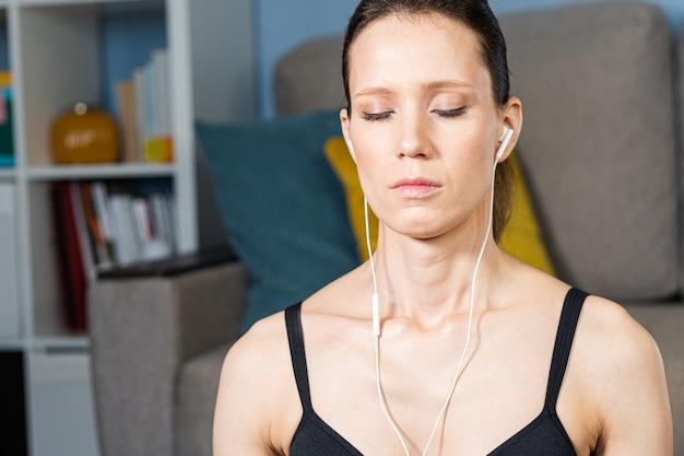 Ciérrese encima del retrato de la mujer joven relajada atractiva que medita y escucha música con los auriculares en casa. chica con ojos cerrados
