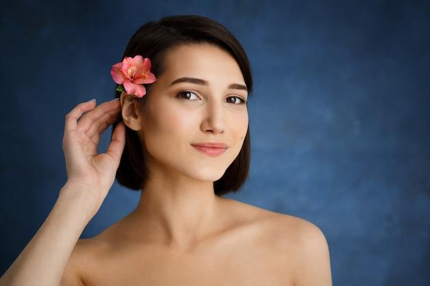 Ciérrese encima del retrato de la mujer joven tierna con la flor rosada en pelo sobre la pared azul