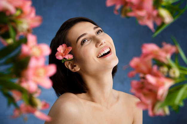 Ciérrese encima del retrato de la mujer joven tierna con las flores rosadas blured sobre la pared azul