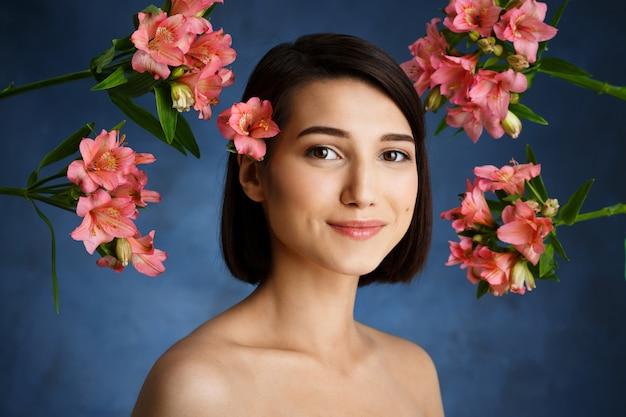 Ciérrese encima del retrato de la mujer joven tierna con las flores rosadas sobre la pared azul