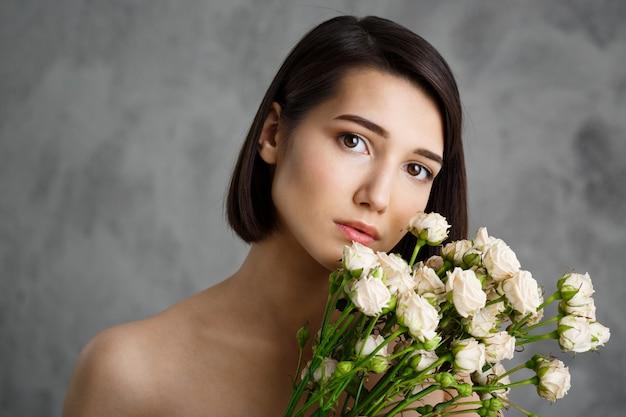 Ciérrese encima del retrato de la mujer joven tierna con las flores sobre la pared gris