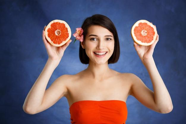 Ciérrese encima del retrato de la mujer joven tierna que sostiene la naranja cortada sobre la pared azul