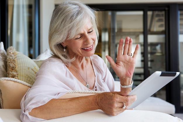 Ciérrese encima del retrato de la mujer mayor feliz en casa con la tableta de la pantalla táctil