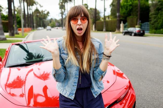 Ciérrese encima del retrato de la mujer morena sorprendida que se sienta en el capó del coche deportivo convertible rojo asombroso en california.