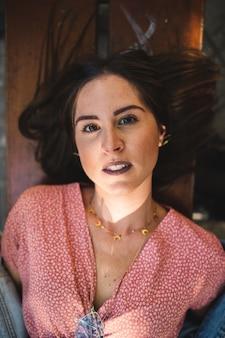 Ciérrese encima del retrato de la mujer que miente en un banco de madera con los accesorios, el collar de oro de la luna, los pendientes y los dientes blancos perfectos. belleza y moda. cosmética y cuidado de la piel.