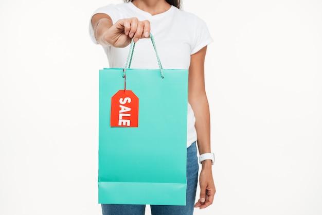 Ciérrese encima del retrato de una mujer que muestra el bolso de compras