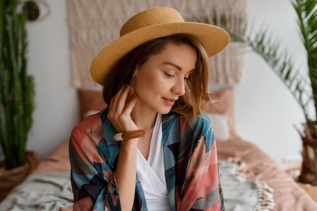 Ciérrese encima del retrato de la mujer romántica hermosa en el sombrero de paja que se enfría sobre interior bohemio