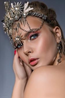 Ciérrese encima del retrato de una mujer rubia hermosa joven que lleva una corona y bisutería sobre un fondo gris.