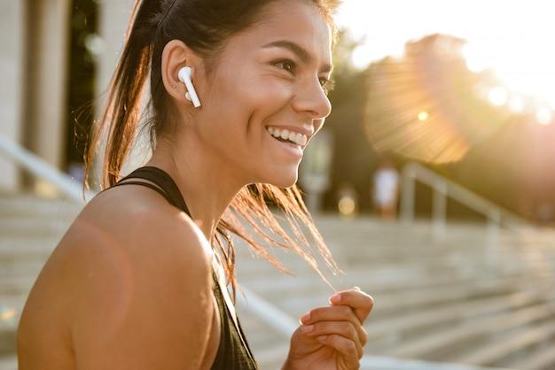 Ciérrese encima del retrato de una mujer sonriente de la aptitud en auriculares
