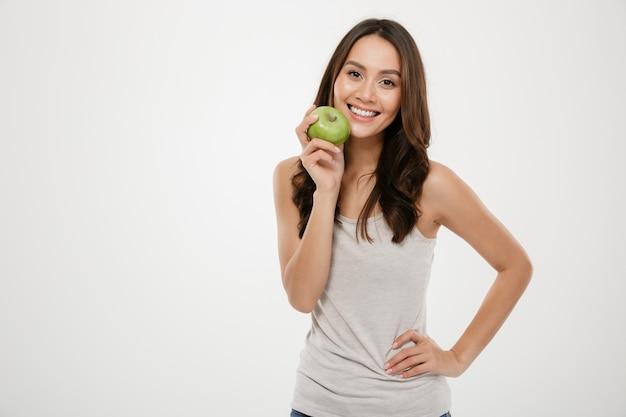 Ciérrese encima del retrato de la mujer sonriente con el pelo castaño largo que mira en cámara con la manzana verde en la mano, aislada sobre blanco