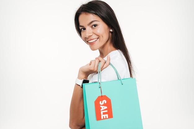 Ciérrese encima del retrato de una mujer sonriente que sostiene el bolso de compras
