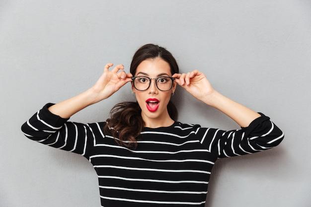 Ciérrese encima del retrato de una mujer sorprendida en lentes