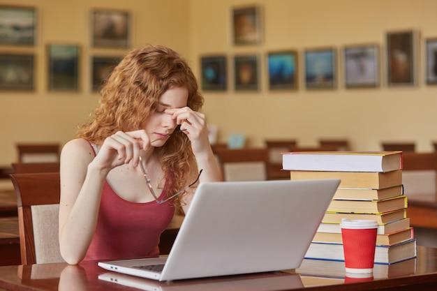 Ciérrese encima del retrato de la mujer triste axhuasted que se siente cansada que se sienta a la mesa en sala de lectura con la computadora portátil, estando con sus anteojos apagados, mantiene los dedos en la nariz, parece infeliz. concepto de educación y universidad.