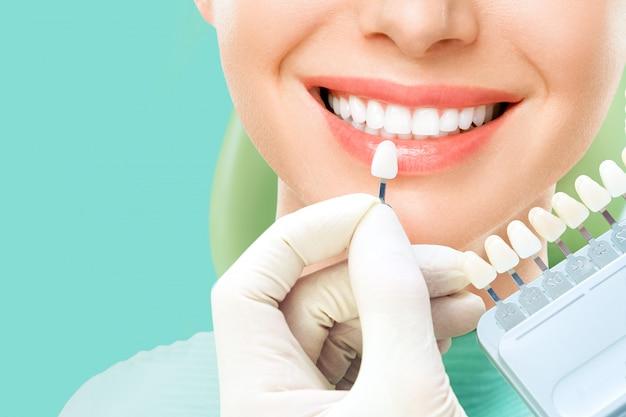Ciérrese encima del retrato de mujeres jovenes en silla del dentista, verifique y seleccione el color de los dientes. blanqueamiento de dientes