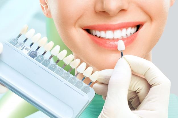 Ciérrese encima del retrato de mujeres jovenes en silla del dentista, verifique y seleccione el color de los dientes. dentista realiza el proceso de tratamiento en consultorio dental. blanqueamiento dental