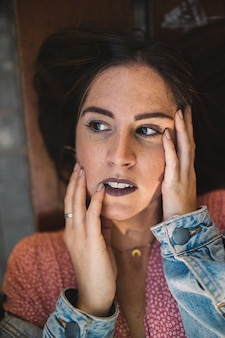 Ciérrese encima del retrato de las mujeres que tocan su cara con las manos, mintiendo en un banco de madera con los accesorios, el collar de oro de la luna, los pendientes y los dientes blancos perfectos. belleza y moda. cosmética y cuidado de la piel.