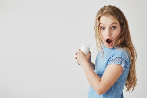 Ciérrese encima del retrato de la niña apuesta divertida con el pelo claro con la expresión sorprendida, sosteniendo el vaso de leche con las manos.