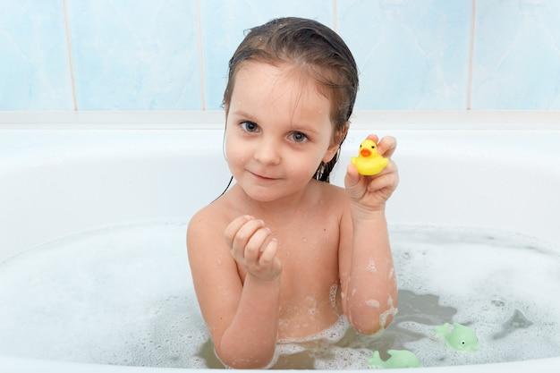 Ciérrese encima del retrato de la niña encantadora feliz que se sienta en bañera juega con el pato amarillo en cuarto de baño.