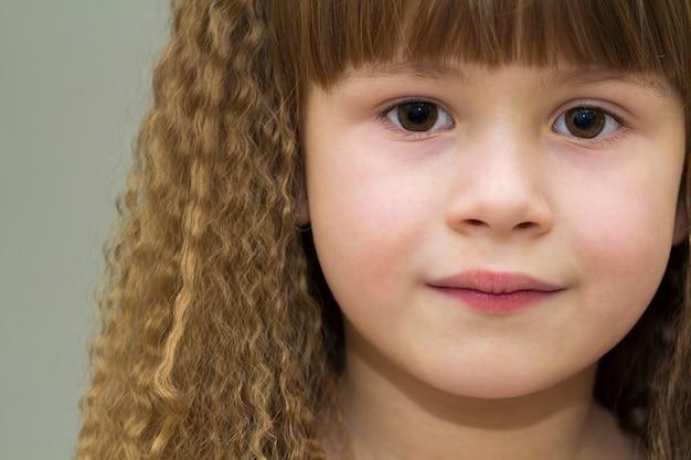 Ciérrese encima del retrato de la niña sonriente feliz con el pelo grueso hermoso