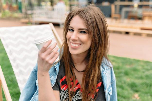 Ciérrese encima del retrato de una niña sonriente con el pelo largo oscuro y una sonrisa encantadora vestida con chaqueta de mezclilla. ella está mirando a la cámara con una gran sonrisa abierta y sostiene una taza de café. hermosa chica en el parque