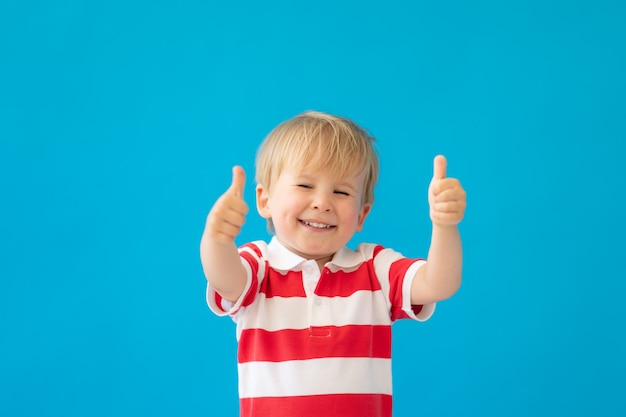 Ciérrese encima del retrato del niño feliz que lleva la camisa rayada que muestra los pulgares contra la pared azul.
