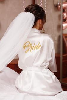 Ciérrese encima del retrato de la novia elegante en el traje blanco con velo largo con la vista posterior de la inscripción