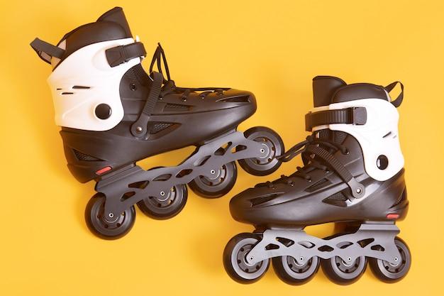 Ciérrese encima del retrato de los patines rodantes adultos aislados sobre el estudio amarillo