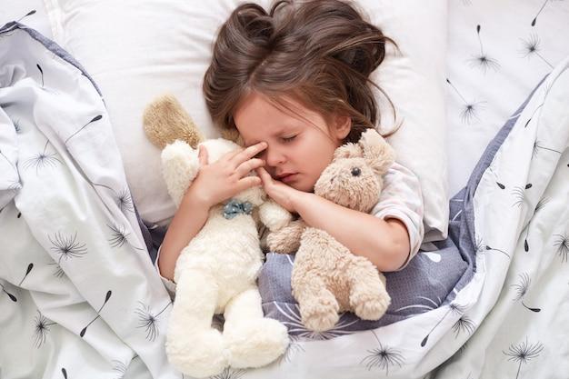 Ciérrese encima del retrato de la pequeña niña caucásica linda abraza el oso de peluche suave y el juguete del perro. retrato de niño dulcemente dormido con chupete