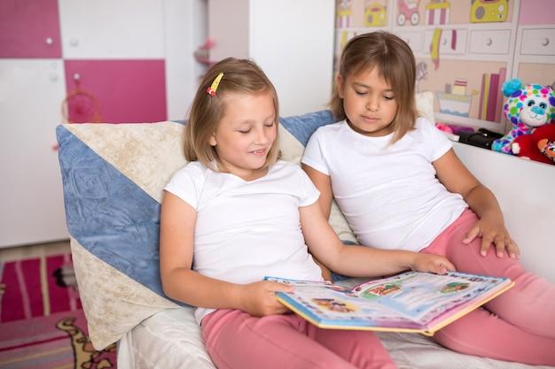 Ciérrese encima del retrato de las pequeñas muchachas adorables caucásicas que leen los libros juntos en dormitorio acogedor