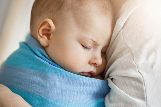 Ciérrese encima del retrato del pequeño niño inocente, durmiendo en las manos de la madre en honda azul del bebé. escena bastante y relajante. familia, concepto de estilo de vida.