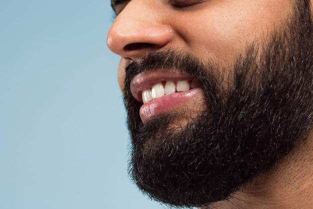 Ciérrese encima del retrato del rostro del joven hindú con barba, dientes blancos y labios en la pared azul. sonriente. las emociones humanas, la expresión facial, el concepto publicitario. espacio negativo.