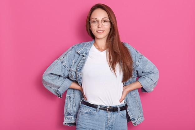 Ciérrese encima del retrato de la señora joven con la ropa y las gafas del dril de algodón, soportes que sonríe aislado sobre estudio rosado, mantiene las manos en las caderas, mirando directamente a la cámara. moda, gente, concepto de jeans