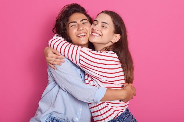 Ciérrese encima del retrato de las señoras, los amigos o las hermanas positivos que se colocan uno al lado del otro, que tienen un abrazo cálido, que presenta con sonrisas agradables, aisladas sobre fondo rosado. concepto de amistad y felicidad.