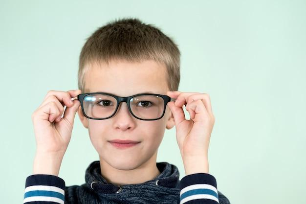 Ciérrese encima del retrato de los vidrios que llevan de un escolar del niño.
