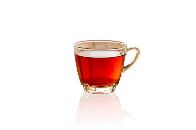 Ciérrese encima de la taza blanca del té negro en aislado