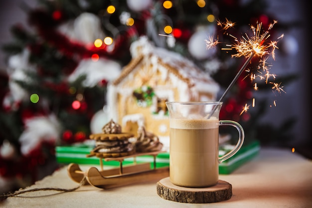 Ciérrese encima de la taza con café y leche en una mesa de madera, casa de pan de jengibre y luces y decoraciones de navidad