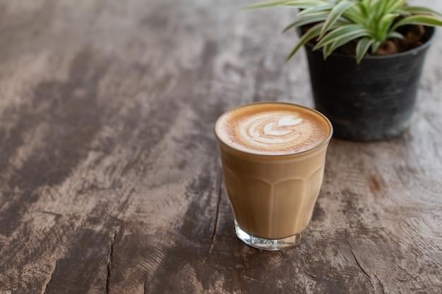 Ciérrese encima de una taza de cristal de café del arte del latte en la tabla de madera