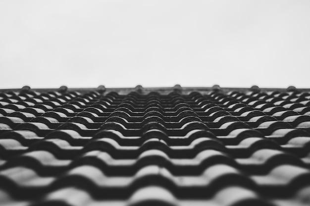 Ciérrese encima de la teja de tejado del foco selectivo b&w de la casa.