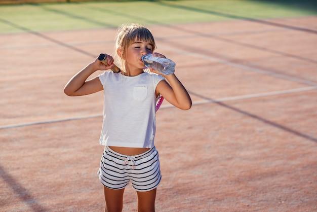 Ciérrese encima del tiro del agua potable de la niña divertida de la botella después del entrenamiento duro del tenis en la corte al aire libre al atardecer. deporte, concepto de salud.