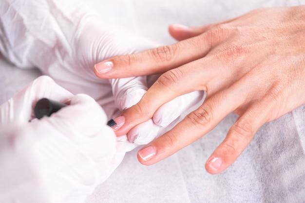 Ciérrese encima de tiro de un cosmetólogo que aplica esmalte de uñas al clavo femenino en el salón del clavo.
