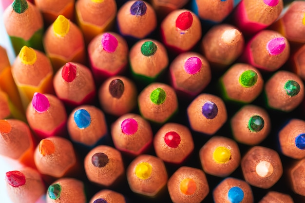 Ciérrese encima del tiro macro de las extremidades del lápiz de la pila del lápiz del color en el fondo blanco.