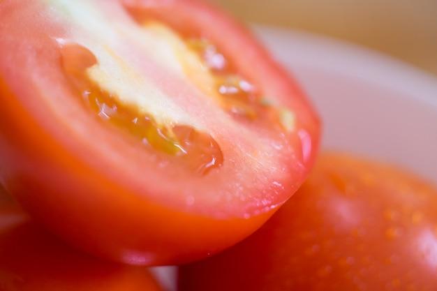 Ciérrese encima del tiro de tomates frescos en la tajadera de madera. foco selectivo.