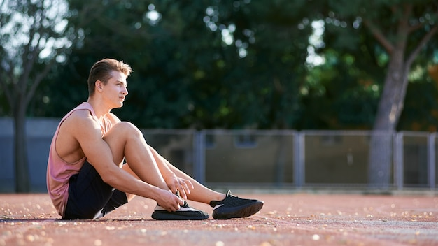 Ciérrese encima del tiro del varón joven del corredor del atleta que estira su pierna en circuito de carreras en estadio, preparándose para resolverse. hombre caucásico haciendo ejercicio al aire libre con ropa deportiva azul. deporte, gente, estilo de vida