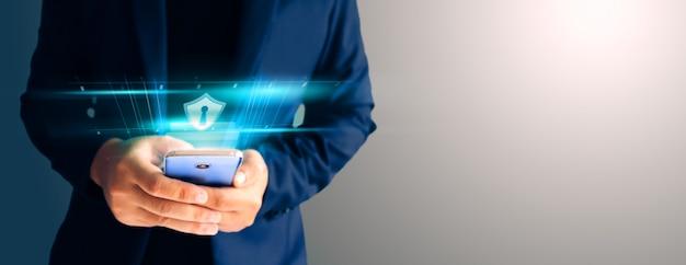 Ciérrese encima del traje azul formal del hombre de negocios utilice sostenga el teléfono inteligente en la oscuridad y copie el espacio. utilice la huella digital para desbloquear la seguridad del teléfono inteligente.