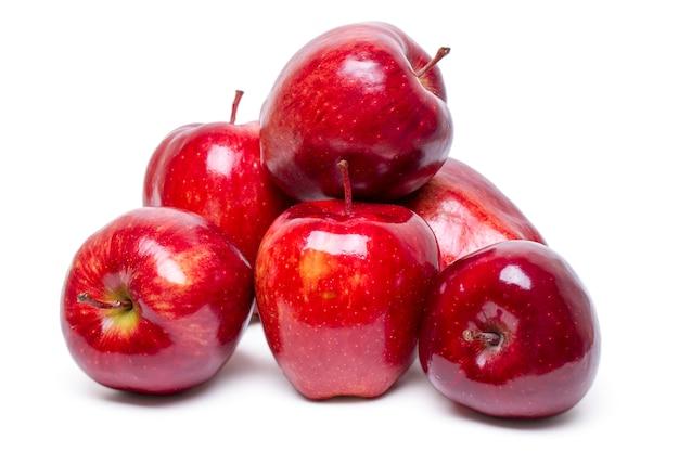 Ciérrese encima de la vista de algunas manzanas rojas aisladas en un fondo blanco.