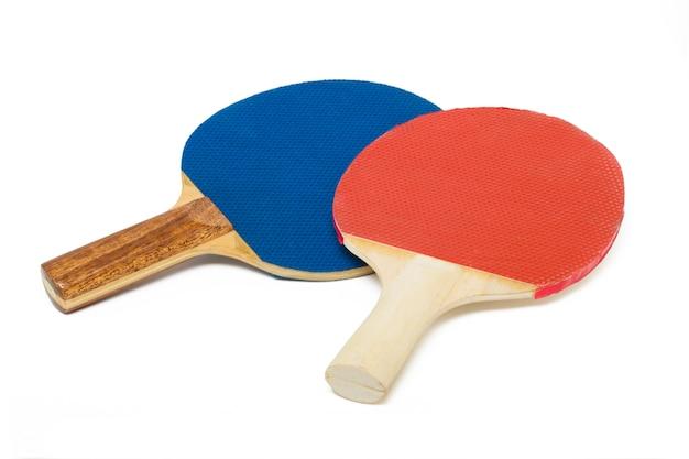 Ciérrese encima de la vista de dos raquetas del ping-pong aisladas en un fondo blanco.