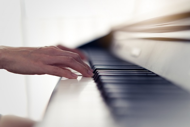 Ciérrese encima de la vista de las manos de la mujer que juegan el piano electrónico en casa.