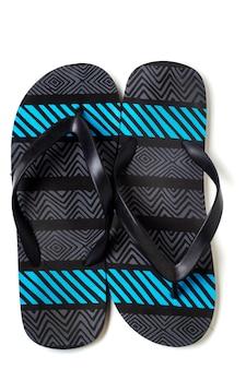 Ciérrese encima de vista de un par de sandalias de la playa aisladas en un fondo blanco.